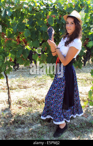 Young woman holding a grape in her hands - Stock Photo