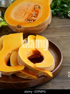 fresh raw pumpkin sliced on a wooden table - Stock Photo