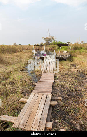 Motor boats moored ready for exploring waterways on a river safari in the Okavango Delta, Botswana - Stock Photo