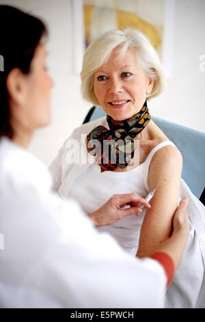 Elderly woman receiving vaccination against influenza. - Stock Photo