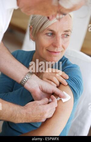 Senior woman receiving against influenza. - Stock Photo