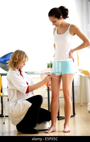 Doctor measuring the thigh of a female patient with tape measure. - Stock Photo