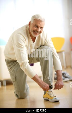Man lacing up his shoes. - Stock Photo