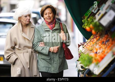 Woman and elderly woman walking in the street. - Stock Photo