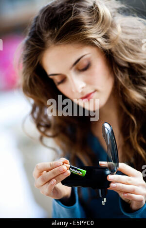 Woman using charger for rechargeable batteries. - Stock Photo
