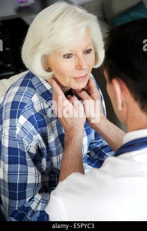 General practitioner palpating the throat of a patient. - Stock Photo