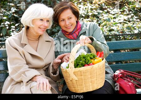 Woman and elderly woman sitting on bench. - Stock Photo