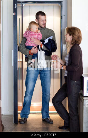 Father taking his 10-month-old baby to a nany. - Stock Photo