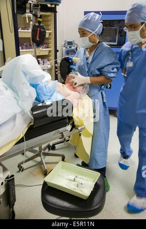 Patient under general anesthesia, with respiratory assistance mask. - Stock Photo