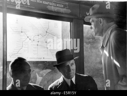 Passengers look at a map of the Berlin Metro in a glass case in Berlin, Germany, September 1943. The Nazi news report - Stock Photo