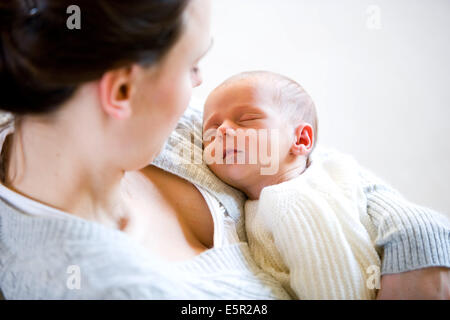 3 weeks old baby with his mother. - Stock Photo