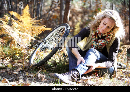 Woman suffering from a pain in the calf. - Stock Photo