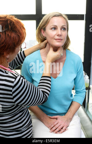 General practitioner palpating the lymphatic glands of a patient during medical consultation. - Stock Photo