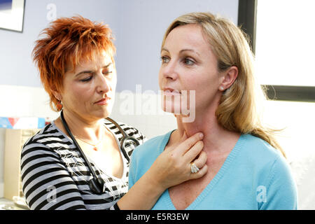 Doctor examining the thyroid gland of a patient. - Stock Photo