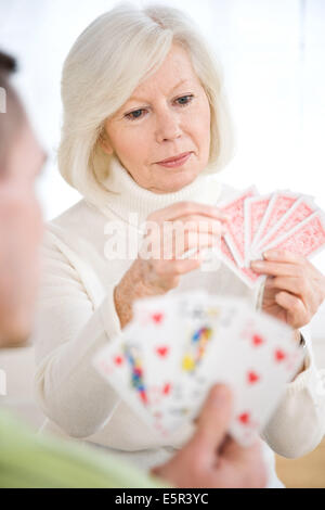 Elderly woman playing cards. - Stock Photo