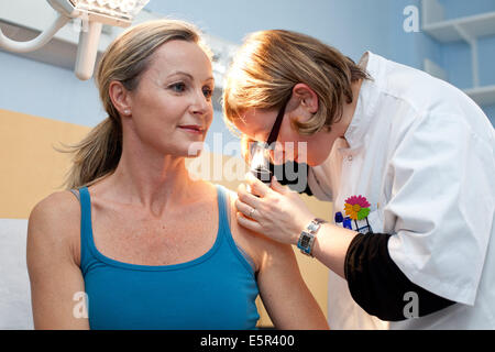 Dermatologist examining skin of female patient with dermatoscope, Limoges hospital, France. - Stock Photo