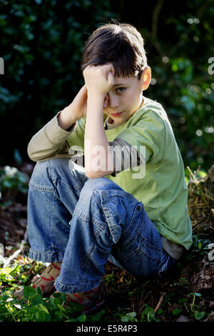 8 year old boy sitting outdoor. - Stock Photo