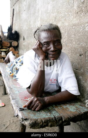 Elderly woman resting in the family house of a poor area of Monrovia (WestPoint shantytown), Liberia. - Stock Photo