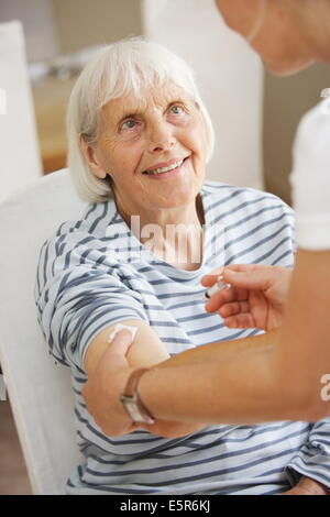 80 year old woman receiving vaccination against flu. - Stock Photo