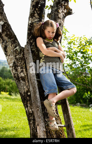 Sullen 7 year old girl on ladder. - Stock Photo