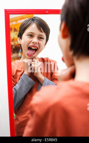 8 year old boy misbehaving. - Stock Photo