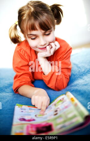 7 year old girl reading toy catalog. - Stock Photo