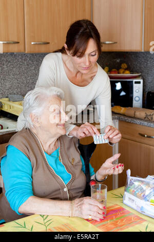 Woman assisting 94 years old woman taking medication. - Stock Photo