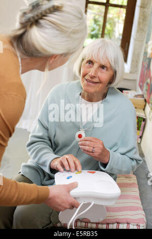 Emergency call button, elderly woman wearing a remote assistance unit at home. - Stock Photo