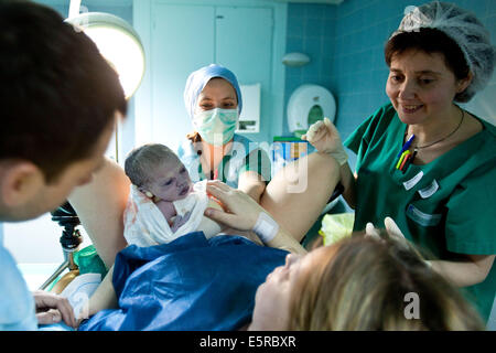woman giving birth midwife nurse and partner in attendance ...