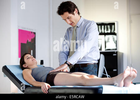 Doctor examining abdomen of female patient by palpation. - Stock Photo