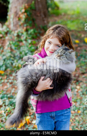 7 years old girl with a cat. - Stock Photo