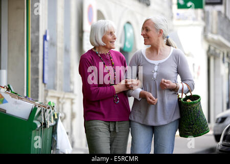 Woman taking 80 year old woman for a walk. - Stock Photo