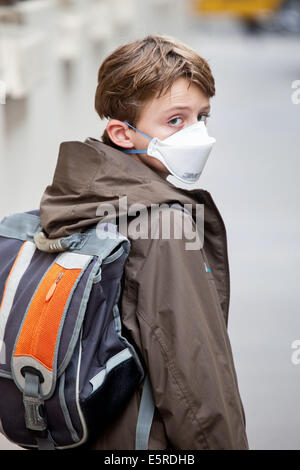 9 year old boy wearing a respiratory protective mask on street. - Stock Photo