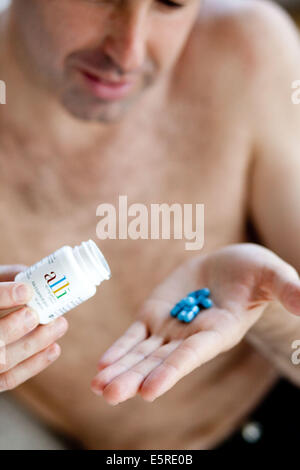 Man taking Alli medicine, Alli is a half-dose version of the diet drug Xenical (Orlistat) produced by GlaxoSmithKline - Stock Photo