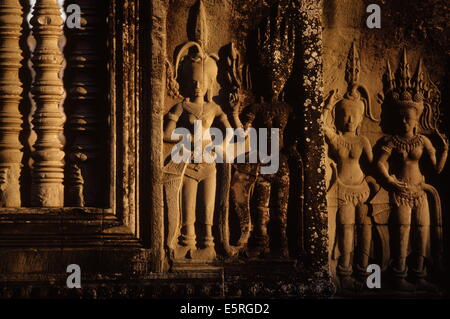 Carvings of apsaras, celestial dancers who entertain the gods, on a gallery wall at Angkor Wat, Cambodia. - Stock Photo
