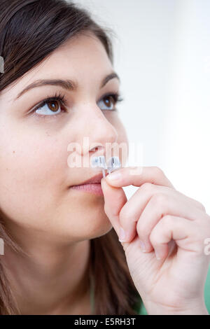 Woman using a nasal filter Nosecaps® against allergies, pollution or snoring. - Stock Photo