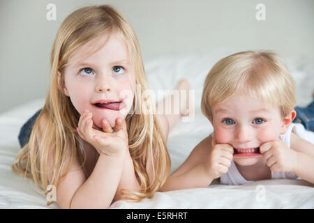 Brother and sister making faces. - Stock Photo