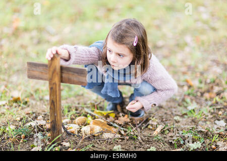 5 year old girl at the side of the grave of her pet. - Stock Photo