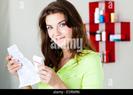 Woman reading medicine instruction sheet. - Stock Photo