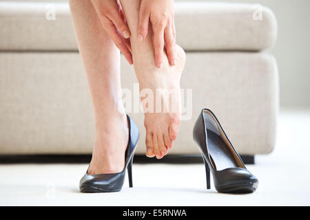 Woman suffering from a pain in the ankle. - Stock Photo