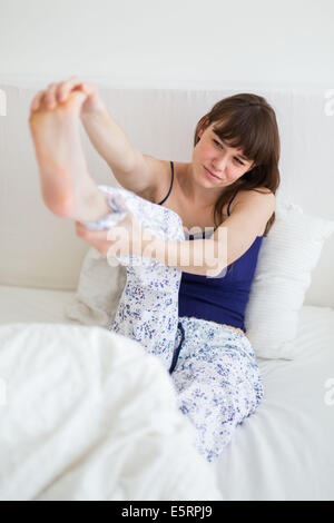 Woman suffering from a cramp in the foot. - Stock Photo