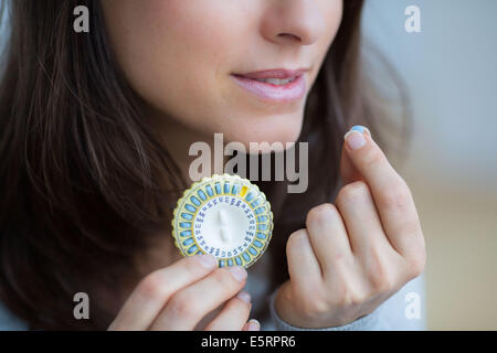 Woman taking an hormone replacement therapy pills. - Stock Photo