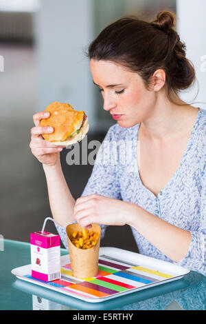 Woman eating hamburger and french fries. - Stock Photo