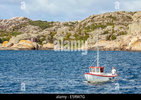 Man on fishing boat sailing in the Archipelago near the island of Stora Dyrön, Tjörn , Bohuslän, Västra Götaland - Stock Photo