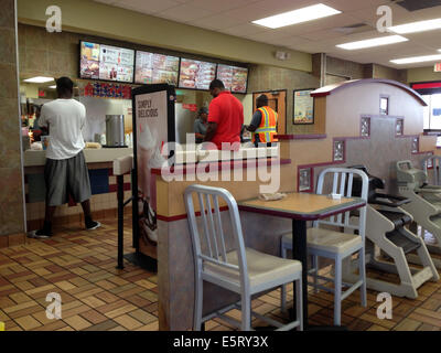 People waiting at the counter for their food at a fast food restaurant - Stock Photo