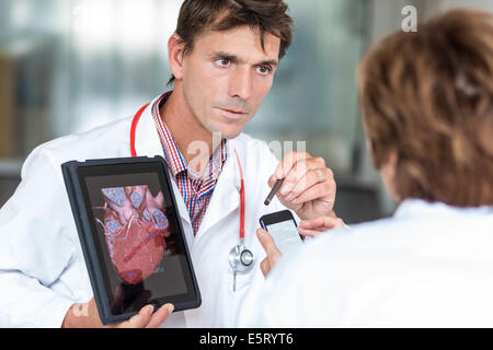 Doctors using a tablet PC and Iphone®. - Stock Photo
