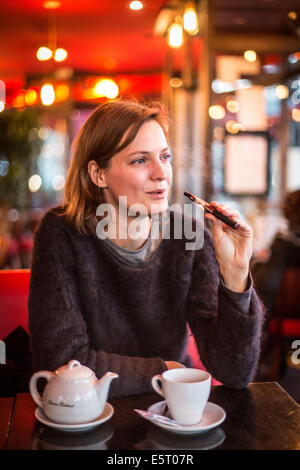 Woman smoking electronic cigarette in a bar. - Stock Photo