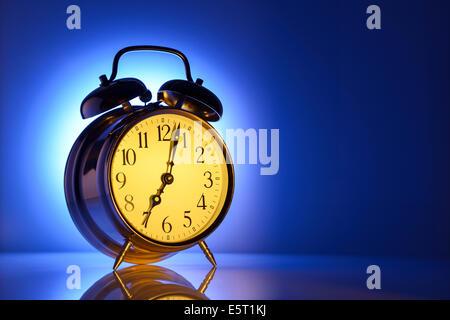 A classic alarm clock set for 7am - Stock Photo