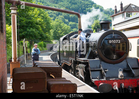 A steam locomotive taking on water at Llangollen station, Denbighshire, Wales. - Stock Photo