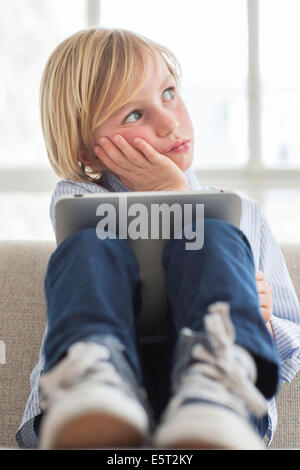 7 year old boy using tablet computer. - Stock Photo
